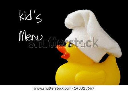 Whimsical cooking concept of little rubber ducky wearing a chef's hat (made of fleece fabric).  Macro on black background with text. - stock photo