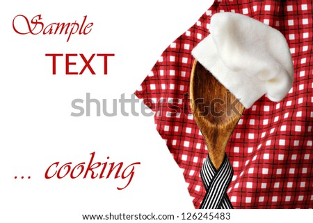 Whimsical cooking concept of vintage wooden spoon 'wearing' a chef's hat with red checkered napkin in soft focus as background.  Macro on white background with copy space. - stock photo