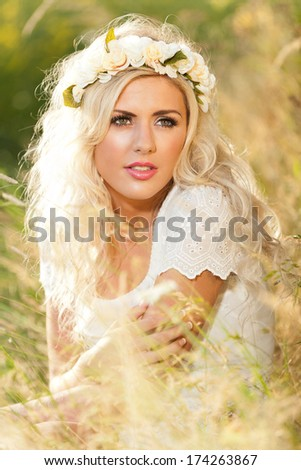 Whimsical image of beautiful woman in field with flowers in hair - stock photo