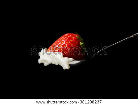 Whipped cream and a strawberry in a silver spoon on black background - stock photo