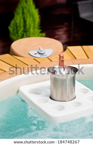 Whirlpool full of water with tray carrying bottle of champagne - stock photo