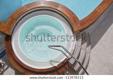 Whirlpool jacuzzi with wooden steps and pool. View from above. - stock photo