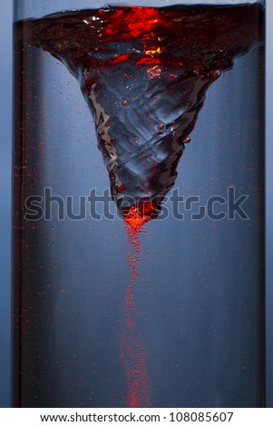 whirlpool with red mist - vortex in a column of water - stock photo