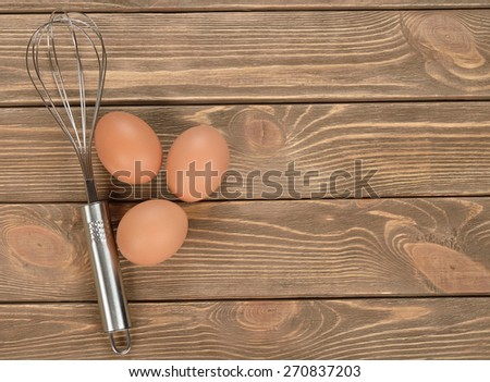 Whisk and eggs on brown background, top view - stock photo