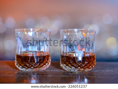 Whiskey. Alcohol drinks and cocktails on bar. colored light - stock photo
