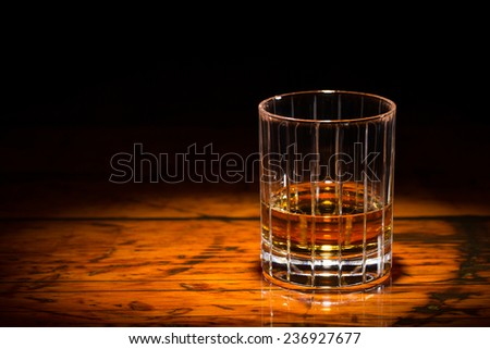 Whiskey and Wood - Liquor in a straight-cut tumbler on a textured wooden table.  Spot light focused on the glass.  Copy space on left.  Upper frame fades to black. - stock photo