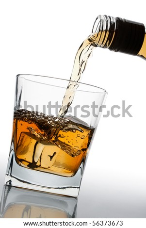 whiskey being poured into a glass - stock photo