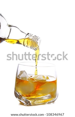 whiskey being poured into glass full of ice cubes - stock photo