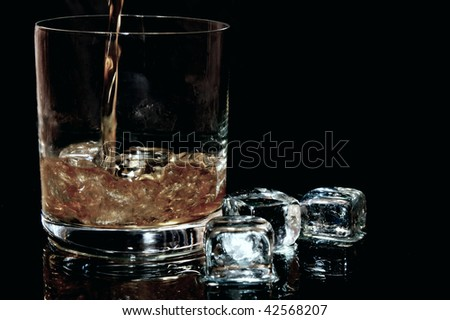 Whiskey flows into a glass with ice cubes to the left against black background in the horizontal format - stock photo