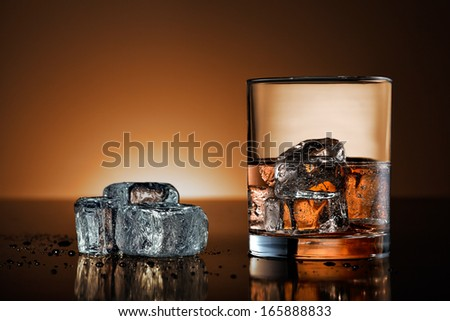 Whiskey glass and ice cubes on black surface with warm background - stock photo