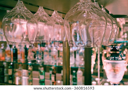 Whiskey glass defocus on Bottles of whiskey at the bar background , process in vintage style pink tone - stock photo