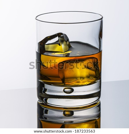 whiskey glass with ice cubes and reflection drink alcohol and grey gradient background - stock photo