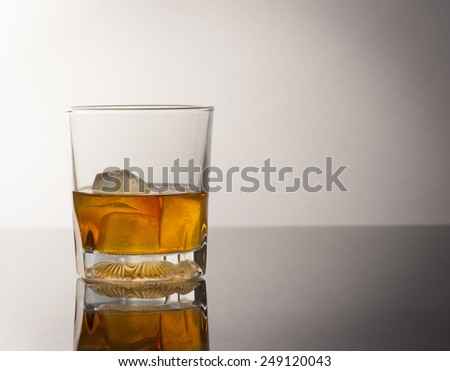 whiskey glass with ice cubes and reflection drink alcohol on grey gradient background - stock photo