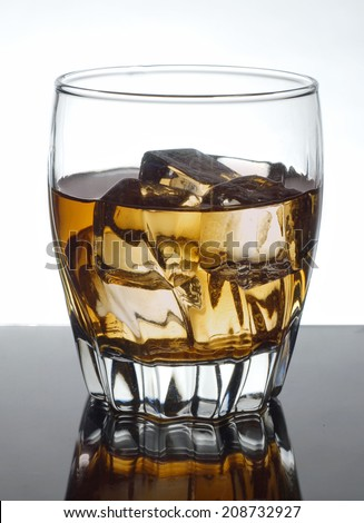 Whiskey in a clear glass on ice sitting on a reflective black table isolated on white. The alcoholic drink is a whiskey on the rocks and is a popular way to enjoy scotch, bourbon, and other whiskies.  - stock photo