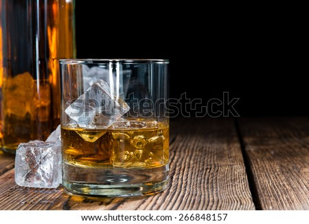 Whiskey in a glass with ice cubes on wooden background - stock photo