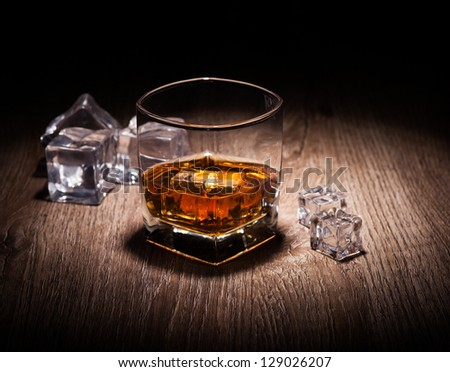 whiskey in glass on wooden table - stock photo
