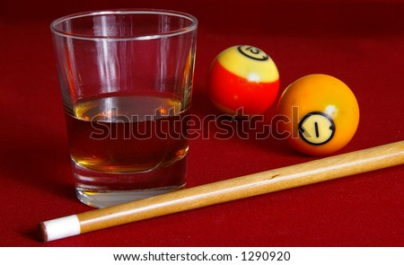 Whiskey on a pool table with cue and balls. - stock photo