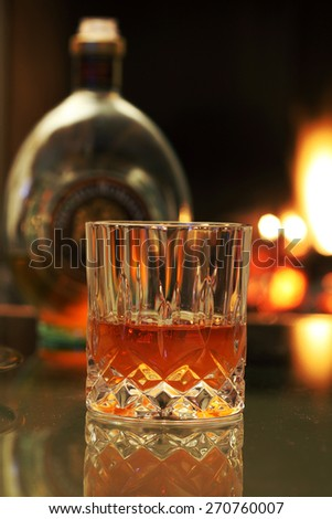 Whiskey on the rocks glass  and whiskey bottle near the fireplace - stock photo
