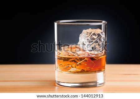 Whiskey on the rocks on wooden table - stock photo
