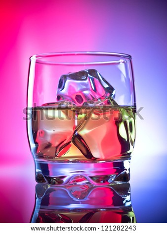 Whiskey on the rocks over vibrant background - stock photo