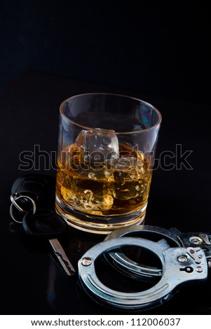 Whiskey on the rocks with car key and handcuff against a black background - stock photo