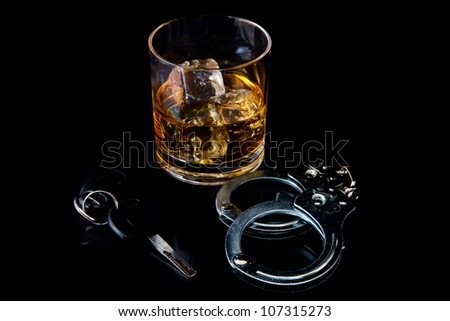 Whiskey on the rocks with handcuff and car key against a black background - stock photo