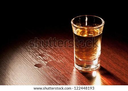 Whiskey shot in a dark bar. - stock photo