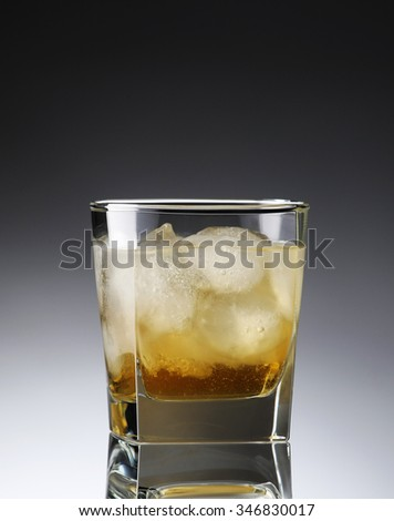 whiskey with ice in a sweaty glass on gradient background - stock photo