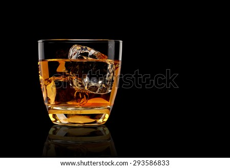 Whiskey with ice in glass isolated on black background with clipping path  - stock photo