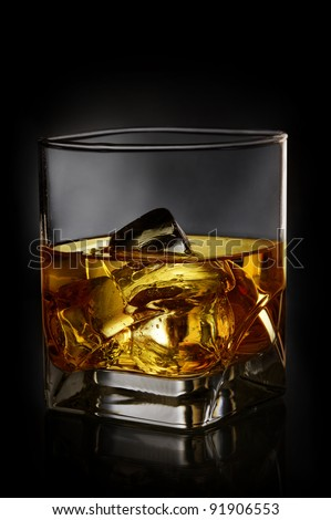 Whiskey with ice in glass on black background - stock photo