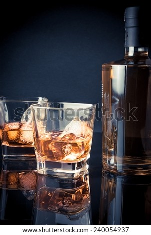whiskey with ice in glasses in front of bottle on black background and light tint blue, with reflection - stock photo
