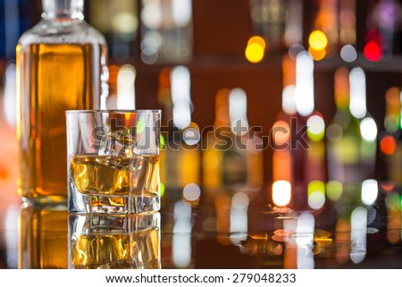 Whiskey with ice on bar desk - stock photo