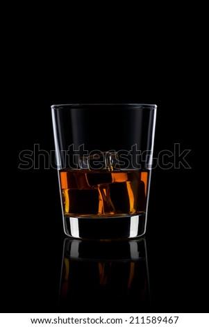 Whiskey with ice on black - stock photo