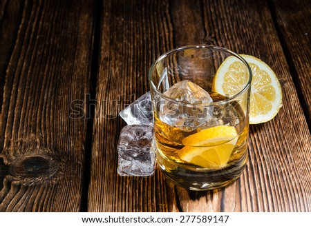Whiskey with lemon and ice cubes on rustic wooden background - stock photo