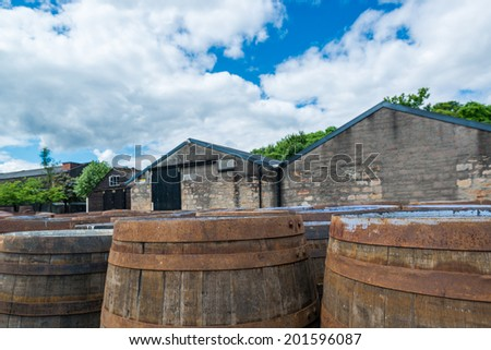 Whisky barrels in front of sheds at a typical Scottish distillery  - stock photo