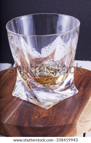 Whisky glass over wooden plate, vertical image - stock photo