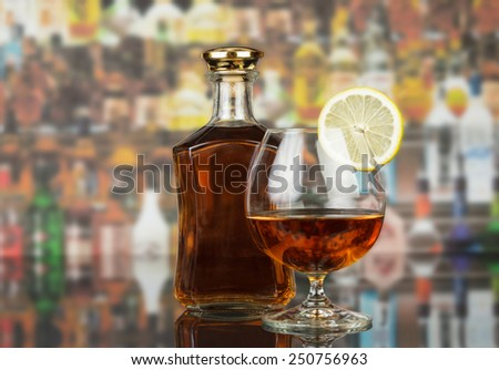 Whisky in glasses and lemon on bar background - stock photo