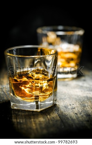 Whisky or Whiskey, vintage style, on a wooden plate - stock photo