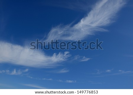 Whispy white clouds in a blue summer sky - stock photo