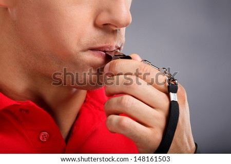 Whistle. Man blowing a whistle - stock photo