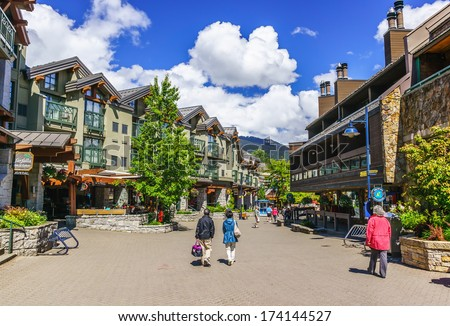 WHISTLER, BRITISH COLUMBIA, CANADA - JUNE 10, 2013: Tourists ramble on the street of Whistler, co-host of the 2010 Olympic Games. It is a Canadian resort town 125 kilometers north of Vancouver. - stock photo