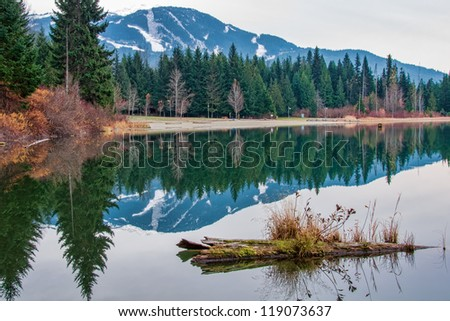 Whistler mountain looks so peaceful reflected in Lost Lake early in the morning. - stock photo