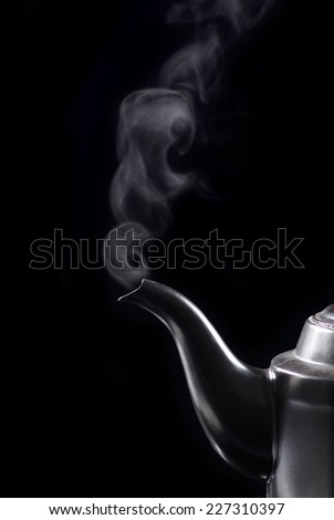 whistling kettle with hot steaming drinking water boiling on the kitchen stove top. - stock photo