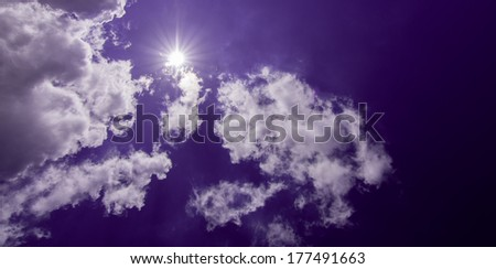 Whit puffy clouds on sunny purple sky - stock photo