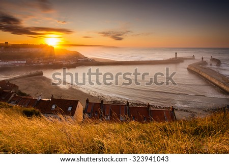 Whitby Harbour at Sunset / Whitby Harbour as the sun goes down shining through the sea mist held back by the cliffs of Sandsend - stock photo
