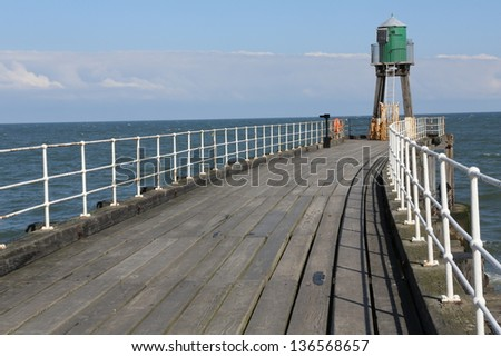 Whitby Pier with old light beacon at the end. - stock photo