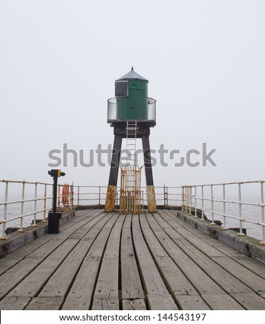 Whitby West Pier and Harbour in thick fog. Yorkshire, England. - stock photo