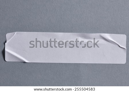 White Adhesive Paper Tag on Grey Cardboard Background with Real Shadow. Sticker Label Close Up. Top View with Copy Space for Text or Image - stock photo