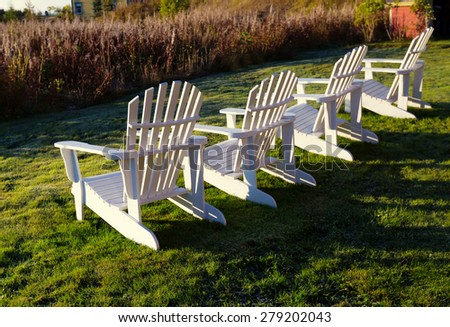 White Adirondack chairs in a row with evening light. - stock photo