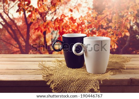 White and black cup with beverage on wooden table over beautiful nature background - stock photo